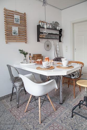 Verschiedene Stühle um gedeckten Kaffeetisch