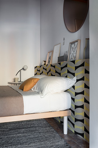 Bed against protruding wall section covered in patterned wallpaper