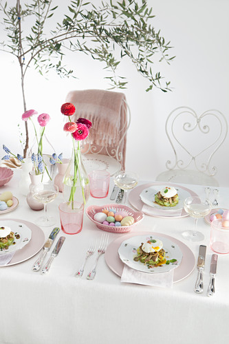 A festive Easter table with flowers in glass vases and Easter eggs in a porcelain basket