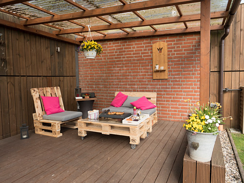 Table and chairs made from pallets on roofed terrace