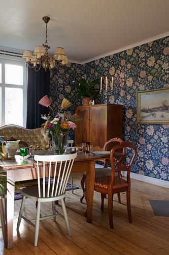 Esszimmer mit verschiedenen alten Möbeln und blauer Tapete