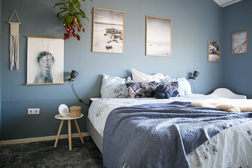 Double bed and large photos in bedroom with grey-blue walls