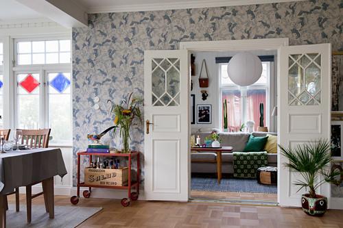 weiße, geöffnete Flügeltür, Vintage Servierwagen und Zimmerpflanze vor tapezierter Wand