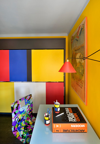 Desk and multicoloured chair in study with yellow wall and colourful wall panels