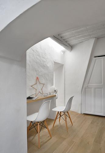 Shell chairs at narrow desk below skylight