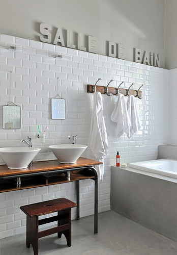 Decorative lettering in French on wall of grey-and-white bathroom