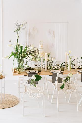 Gedeckter Hochzeitstisch mit Frühlingsblumen, trockenen Zweigen und Cylinderkerzen, im Hintergrund Buffet mit Hochzeitstorte