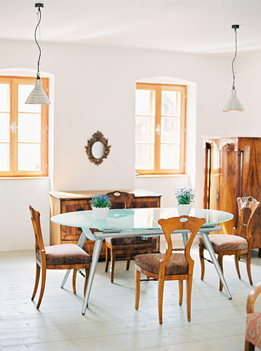 Modern dining table with glass top and Biedermeier furniture in bright dining room