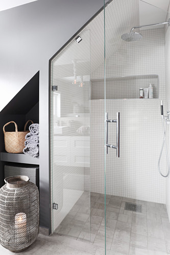 Shower and shelving in niche below sloping ceiling