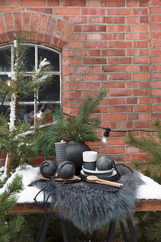 Arrangement of black Christmas decorations and pine branches outside brick house