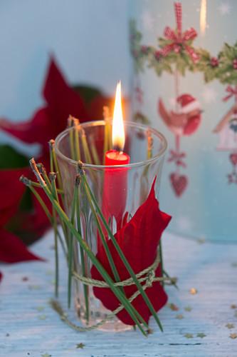 Glas mit Weihnachtsstern und Kiefernnadeln dekoriert, als Windlicht