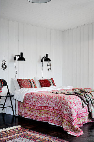 Doppelbett mit geblümter Tagesdecke, schwarze Wandleuchten an weißer Holzverkleidung im Schlafzimmer