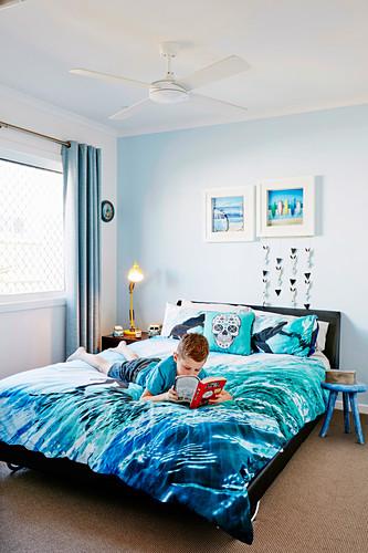 Junge mit Buch liegt auf Bett blauer Bettwäsche