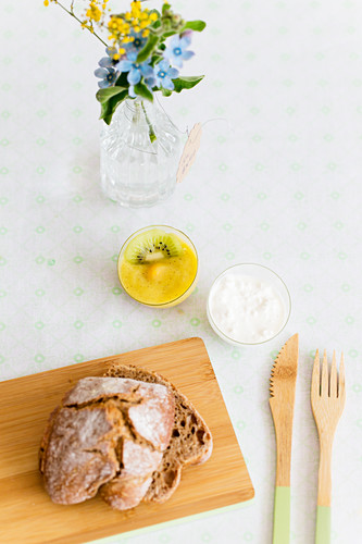 Wooden cutlery, bread on wooden board, mango puree and cottage cheese