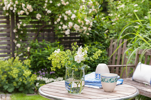 Bouquet of lady's mantle and aquilegia in preserving jar on garden table