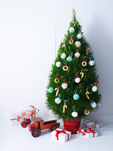 Weihnachtsbaum mit bunten Pompons und Gebäckkringeln
