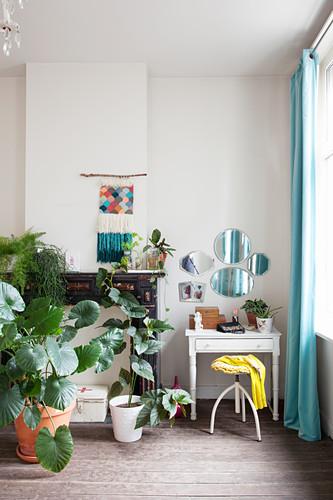 Zimmerpflanzen, stillgelegter Kamin, Makramee, Schubladentisch und Wandspiegel
