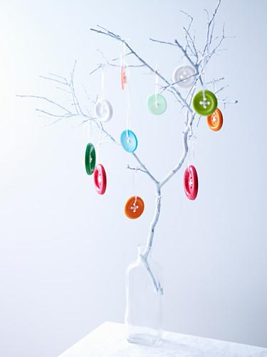 Zweig mit bunten Knöpfen dekoriert