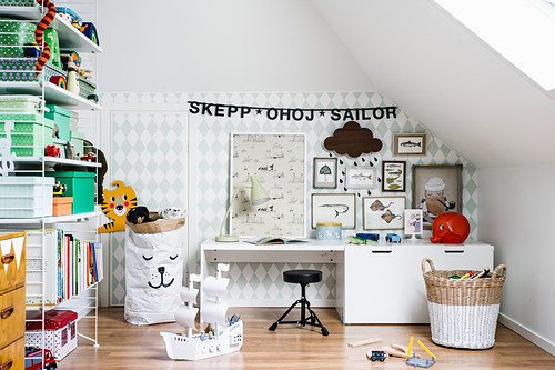 Gallery of pictures and garland of lettering above desk in child's bedroom