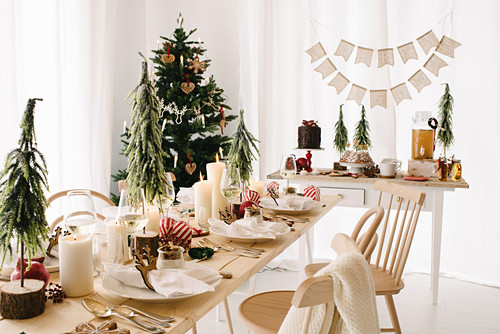 Table festively set with white pillar candles and small Christmas trees