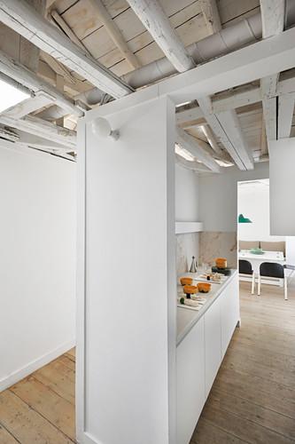 Küche in offenem Wohnraum mit rustikaler Dachkonstruktion