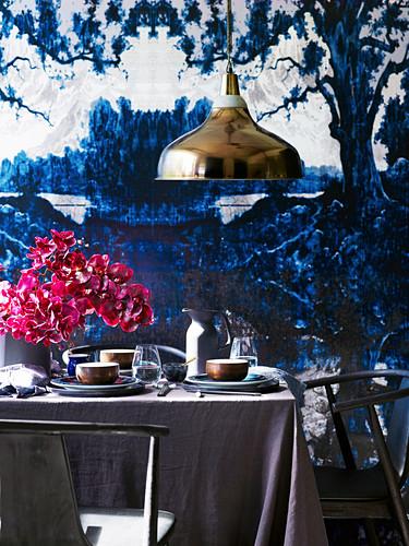 Gedeckter Tisch mit grauer Leinentischdecke und violettem Orchideenstrauss