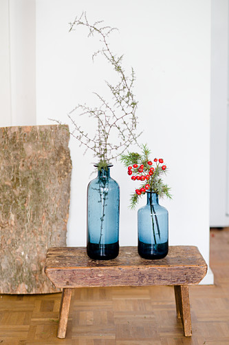 Twigs in two blue vases and on old stool