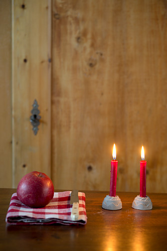 Two lit red candles in cake-shaped candle holders