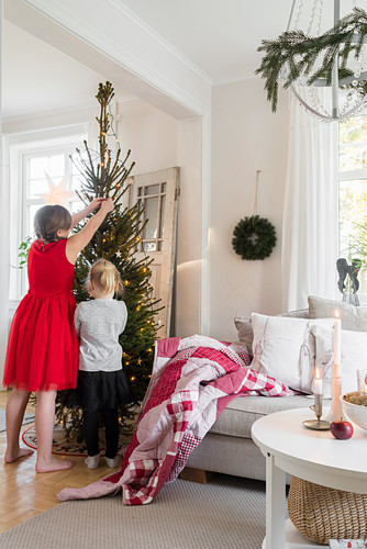 Girls decorating Christmas tree next to sofa in living room
