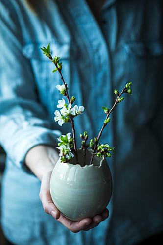 Frau hält Keramikei mit Kirschblütenzweigen als Osterdeko