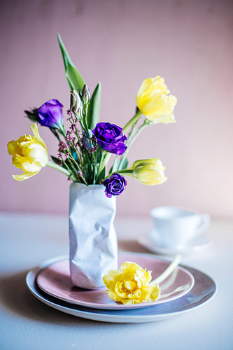 Spring flowers in vase shaped like crushed tin can