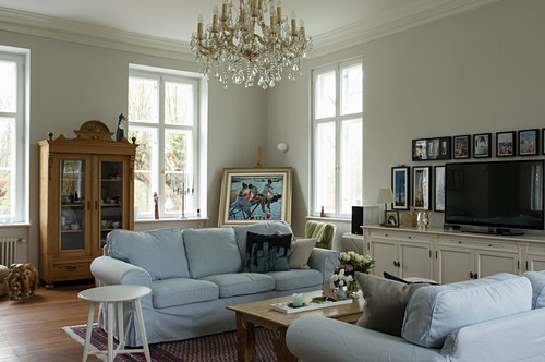 Pale loose-covered sofa, glass-fronted cabinet and chandelier in living room