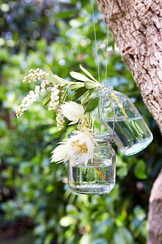 Hängevasen mit Blüten im Garten