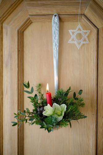 Weihnachtliches Gesteck mit Kerze in einem Schöpflöffel