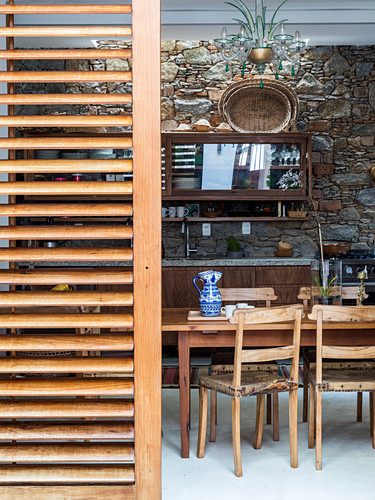 View into rustic dining room with stone wall