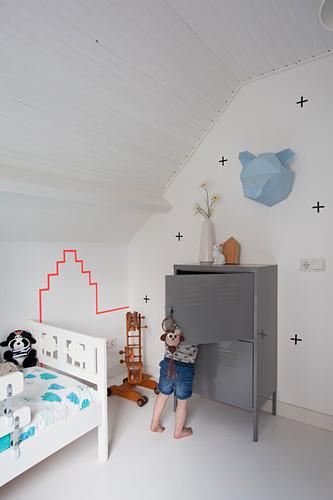 Kind vor grauem Schrank und weißes Bett im Kinderzimmer im Dachgeschoss
