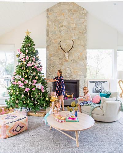 Familie im pastellfarben dekorierten Wohnzimmer mit Weihnachtsbaum