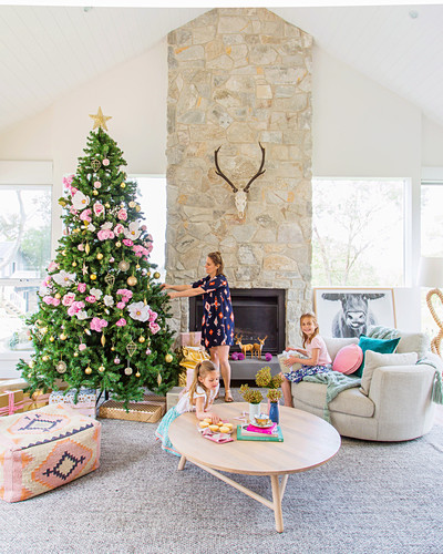 Family in pastel-colored living room with Christmas tree