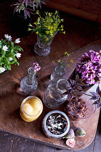 Fruit, chutneys and flowers in glass jars and vases