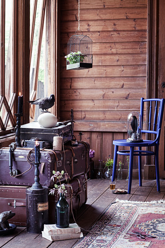 Vintage birdcage, blue chair, stuffed bird and stacked trunks in room with wooden wall