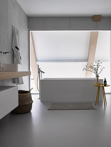 Free-standing bathtub in modern bathroom with glass wall