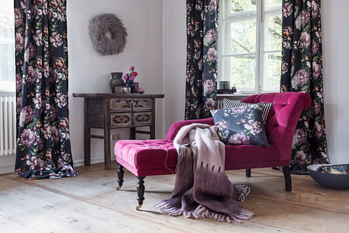Pink recamier in front of windows with dark floral curtains