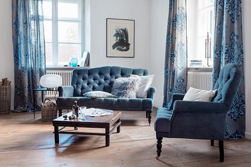 Elegantes Wohnzimmer in Blau mit klassischen Polstermöbeln