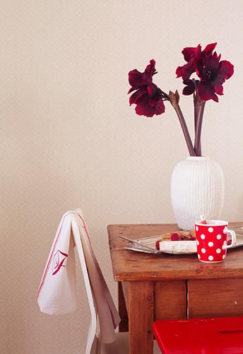 weiße Vase mit Amaryllis auf Holztisch