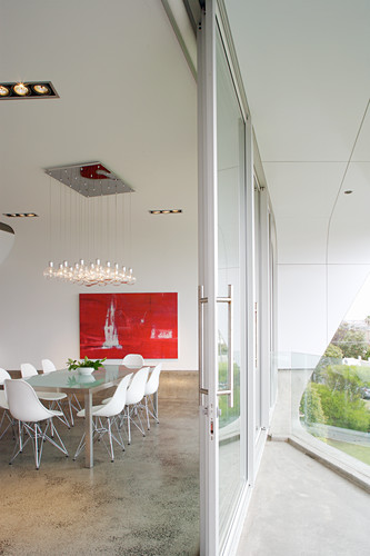 Dining room with glass wall leading onto balcony in futurist house