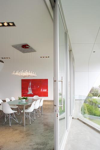 Esszimmer mit Fensterfront zum Balkon eines futuristischen Hauses