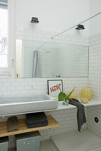 Large mirror above long washstand in bright bathroom