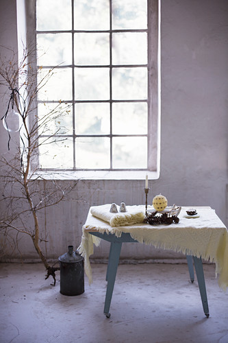 Woollen blankets and wintry accessories on table in front of industrial-style window
