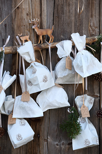 Advent calendar made from sandwich bags on rustic board wall