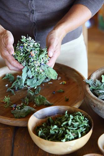 Hände mischen getrocknete Blüten und Blätter zum Tee